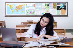 Student writing on books in the classroom Royalty Free Stock Images