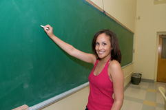 Student writing on Chalkboard Stock Image