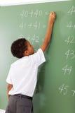 Student writing chalkboard. Elementary school student writing maths answer on chalkboard Stock Photos