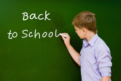 Student writing on the chalkboard.  Stock Photos
