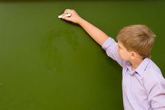 Student writing on the chalkboard.  Stock Images