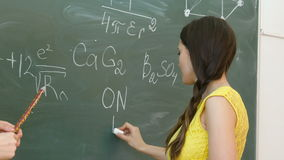 Student writing chemical symbol on blackboard. stock video footage