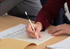 Student writing Chinese characters. Closeup of hands of student using a white pencil to write Chinese characters in a notebook on desk Royalty Free Stock Image