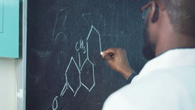 Student writing a formula. Back view of a student writing a chemical formula on the blackboard stock video