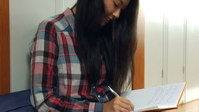 Student writing into her school journal. In the university college stock footage