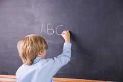 Student writing on large blackboard Stock Image
