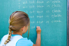 young girl writing lines on chalkboard royalty free stock photo