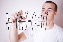 Student writing mathematical exercise in the foreg. Young man in white shirt writes mathematical exercise Royalty Free Stock Photos