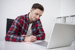 Student writing near laptop. Portrait of a student in a checkered shirt writing in his notebook while sitting near a laptop. Concept of studying Stock Photos