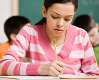 Student writing in notebook in school classroom Stock Image