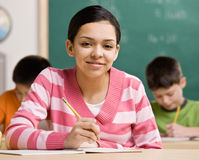 Student writing in notebook in school classroom Stock Photos