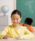 Student writing in notebook in school classroom Royalty Free Stock Photos
