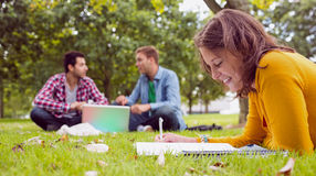Student writing notes with males using laptop at park Stock Images