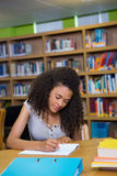 Student writing notes in notepad in the library Stock Photo