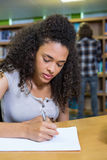 Student writing notes in notepad in the library Stock Images
