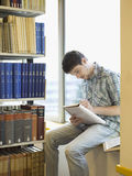 Student Writing Notes On Windowsill In Library. Young male student sitting on windowsill in library and writing notes Royalty Free Stock Photo