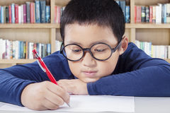 Student writing on the paper in the library Royalty Free Stock Photography