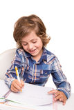 Student writting. Student boy writing for homework at his desk Royalty Free Stock Photography