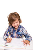 Student writting. Student boy writing for homework at his desk Royalty Free Stock Photos