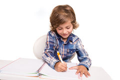 Student writting. Student boy writing for homework at his desk Stock Photo