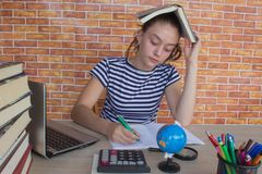 Student, Young Girl working on his homework. Portrait of pretty girl high school student studying and writing. Thoughts, education, creativity concept stock image