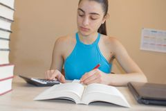 Student, Young Girl write in notebook between books. young student Girl studying lessons Stock Photos