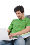 Student - Young man with laptop on bean bag Royalty Free Stock Images