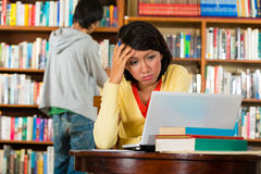 Young Girl in library with laptop Royalty Free Stock Image