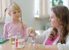 Student zeigt Experiment für das kleine Mädchen stockbilder