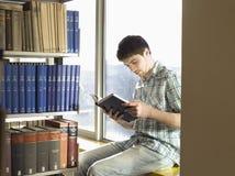Studenta Collegu czytanie W bibliotece Obrazy Stock