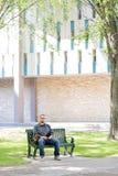 Studenta Uniwersytetu obsiadanie Na ławce Przy kampusem Zdjęcia Royalty Free