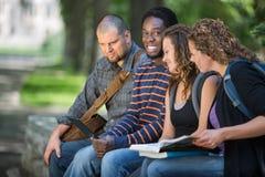 Studenta Uniwersytetu obsiadanie Z przyjaciółmi Na kampusie Obraz Royalty Free