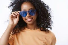 Studentafrofrisur des überzeugten sorglosen attraktiven Afroamerikaners junge, welche die Sonnenbrille trägt Eyewear überprüft stockbild