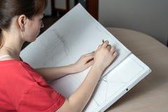 Studentarkitekten förbereder ett utkastarbete, drar en blyertspenna på en vit minnestavla royaltyfri bild