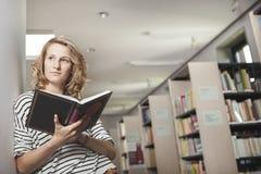 Studente abile con il libro aperto che lo legge nella biblioteca di istituto universitario Fotografia Stock Libera da Diritti