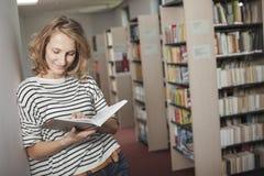Studente abile con il libro aperto che lo legge nella biblioteca di istituto universitario Fotografie Stock