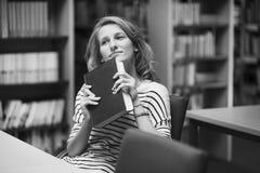 Studente abile con il libro aperto che lo legge nella biblioteca di istituto universitario Immagini Stock