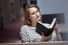Studente abile con il libro aperto che lo legge nella biblioteca di istituto universitario Immagini Stock Libere da Diritti
