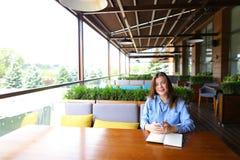 Studente abile femminile che si siede al caffè e che prepara per l'esame con lo smartphone ed il taccuino Fotografia Stock
