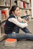 Studente accanto allo scaffale per libri che sembra deprimente Fotografie Stock Libere da Diritti