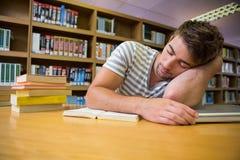 Studente addormentato nella biblioteca Immagine Stock