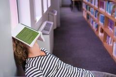 Studente addormentato nella biblioteca con il libro sul suo fronte Immagini Stock