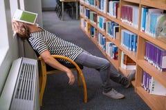 Studente addormentato nella biblioteca con il libro sul suo fronte Fotografie Stock Libere da Diritti