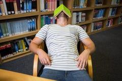 Studente addormentato nella biblioteca con il libro sul suo fronte Fotografie Stock