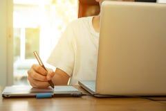 Studente adolescente che lavora al computer portatile sulla tavola di legno Immagini Stock Libere da Diritti