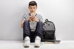 Studente adolescente che pende contro la parete bianca e che per mezzo del telefono Fotografia Stock Libera da Diritti