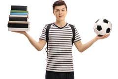 Studente adolescente che tiene una pila di libri e di calcio Fotografie Stock Libere da Diritti