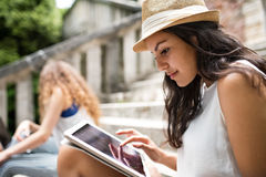 Studente adolescente con la compressa che si siede sui punti di pietra Fotografie Stock