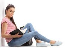 Studente adolescente femminile con un libro che si siede sul pavimento Immagine Stock