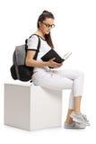Studente adolescente femminile su un cubo che legge un libro Fotografia Stock